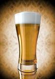 背景淡黄色的啤酒杯 库存照片