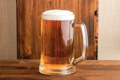 背景淡黄色的啤酒杯 免版税库存照片