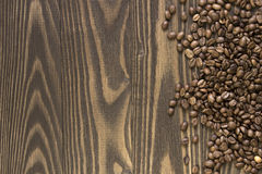 背景溢出了在一张木桌上的咖啡豆 免版税库存照片