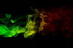 背景烟曲线和波浪雷鬼摇摆乐上色绿色,黄色,在雷鬼摇摆乐音乐旗子红颜色  库存照片