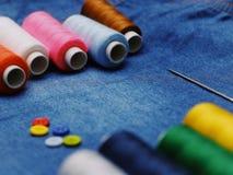 背景牛仔裤织品,螺纹,与螺纹,五颜六色的背景的针 概念缝合的事务,企业织品,缝合的工作 免版税库存照片