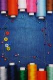 背景牛仔裤织品,螺纹,与螺纹,五颜六色的背景的针 概念缝合的事务,企业织品,缝合的工作 图库摄影