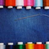 背景牛仔裤织品,螺纹,与螺纹,五颜六色的背景的针 概念缝合的事务,企业织品,缝合的工作 免版税库存图片