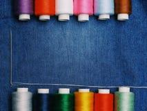 背景牛仔裤织品,螺纹,与螺纹,五颜六色的背景的针 概念缝合的事务,企业织品,缝合的工作 库存照片