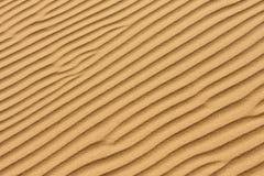 背景理想的沙子纹理 风的打击的消弱的波浪 免版税库存照片