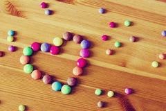 背景用以心脏的形式颜色糖果在葡萄酒定调子的木桌上 免版税库存照片