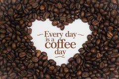 背景由在心脏形状的咖啡豆制成与消息`每天是咖啡天` 免版税库存照片