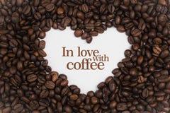 背景由在心脏形状的咖啡豆制成与消息`爱上咖啡` 免版税库存照片