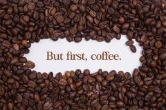 背景由在心脏形状的咖啡豆制成与消息`,但是首先,咖啡 ` 免版税库存图片