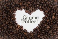 背景由在心脏形状的咖啡豆制成与消息` Gimme更多咖啡! ` 免版税库存图片
