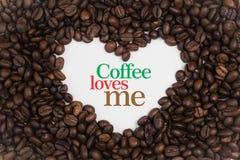 背景由在心脏形状的咖啡豆制成用消息`咖啡爱我` 免版税库存图片