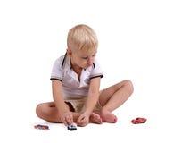 背景男孩查出空白的一点 使用与小玩具汽车的一个逗人喜爱的孩子 童年概念 复制空间 免版税库存图片