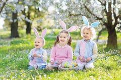 背景男孩逗人喜爱的复活节彩蛋蛋新草绿色隐藏的搜索查出搜索白色 与兔宝宝耳朵和篮子的孩子 免版税库存图片
