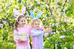 背景男孩逗人喜爱的复活节彩蛋蛋新草绿色隐藏的搜索查出搜索白色 与兔宝宝耳朵和篮子的孩子 图库摄影
