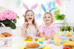 背景男孩逗人喜爱的复活节彩蛋蛋新草绿色隐藏的搜索查出搜索白色 与兔宝宝耳朵和篮子的孩子 库存照片