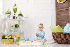 背景男孩逗人喜爱的复活节彩蛋蛋新草绿色隐藏的搜索查出搜索白色 在家使用用复活节彩蛋的可爱的孩子 图库摄影