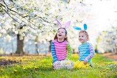 背景男孩逗人喜爱的复活节彩蛋蛋新草绿色隐藏的搜索查出搜索白色 与兔宝宝耳朵的孩子在春天庭院里 免版税图库摄影