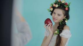 背景画笔关闭查出摄影白色的工作室牙 妇女摄影师与年轻模型一起使用以春天方式用果子在演播室 后台射击 股票录像