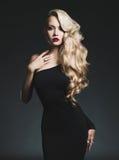 黑背景的典雅的金发碧眼的女人 免版税库存图片