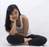 背景的思考逗人喜爱的亚裔的女孩 免版税库存照片