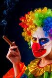 黑背景的疯狂的小丑 妇女抽雪茄 库存照片