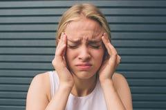 背景的美丽的白肤金发的女孩,恼怒的叫喊的妇女,头疼 顶头一名被注重的妇女的画象对负  免版税库存照片