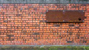 背景的老砖墙与空的生锈的委员会和青苔 免版税库存照片
