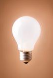 背景米黄查出的电灯泡发光 库存图片