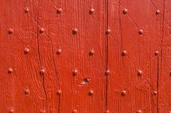 背景纹理风化了与钉子装饰的红色木门 免版税库存图片