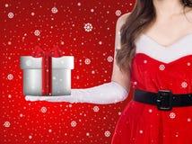 背景美丽的圣诞节逗人喜爱的礼品女孩愉快的帽子藏品查出看起来显示斜向一边的白人妇女年轻人的当前圣诞老人 库存照片