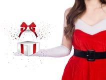 背景美丽的圣诞节逗人喜爱的礼品女孩愉快的帽子藏品查出看起来显示斜向一边的白人妇女年轻人的当前圣诞老人 免版税库存图片