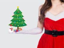 背景美丽的圣诞节逗人喜爱的礼品女孩愉快的帽子藏品查出看起来显示斜向一边的白人妇女年轻人的当前圣诞老人 免版税图库摄影