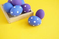 背景美丽的复活节彩蛋节假日污点 在一个盘子的复活节彩蛋鸡蛋的 在立场的鸡蛋 黄色背景 图库摄影