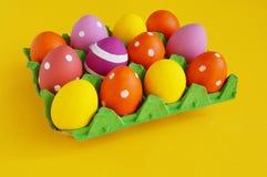 背景美丽的复活节彩蛋节假日污点 在一个盘子的复活节彩蛋鸡蛋的 在立场的鸡蛋 黄色背景 库存照片