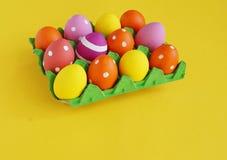 背景美丽的复活节彩蛋节假日污点 在一个盘子的复活节彩蛋鸡蛋的 在立场的鸡蛋 黄色背景 免版税库存图片