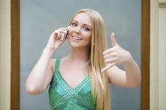 背景美好的女实业家购买权查出我新 做电话我的绿色礼服的性感的少妇gestur 库存图片