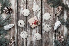 背景老木 冷杉分支,锥体 甜饼干圈子与一件现代礼物的在中心 库存图片