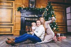 背景能圣诞节使用的例证主题 与一年的白肤金发的男孩的年轻家庭坐木地板反对一棵圣诞树的背景与的礼物的 免版税库存照片