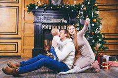 背景能圣诞节使用的例证主题 与一年的白肤金发的男孩的年轻家庭坐木地板反对一棵圣诞树的背景与的礼物的 库存照片