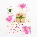 背景能明信片使用的华伦泰 桃红色郁金香、玫瑰、葡萄酒纸牌和在白色背景隔绝的礼物盒 平的位置,顶视图 图库摄影