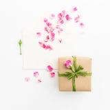 背景能明信片使用的华伦泰 玫瑰和葡萄酒纸牌,在白色背景的礼物盒的瓣 平的位置,顶视图 库存图片