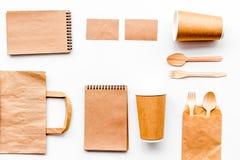 背景色的一次性叉子玻璃塑料集合碗筷透明白色 纸杯,匙子,在包装纸袋子和笔记本顶视图拷贝样式白色的空间嘲笑附近分叉 免版税图库摄影