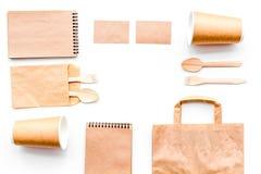 背景色的一次性叉子玻璃塑料集合碗筷透明白色 纸杯,匙子,在包装纸袋子和笔记本顶视图拷贝样式白色的空间嘲笑附近分叉 库存照片