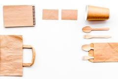 背景色的一次性叉子玻璃塑料集合碗筷透明白色 纸杯,匙子,在包装纸袋子和笔记本顶视图拷贝样式白色的空间嘲笑附近分叉 图库摄影