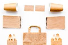 背景色的一次性叉子玻璃塑料集合碗筷透明白色 纸杯,匙子,在包装纸袋子和笔记本顶视图拷贝样式白色的空间嘲笑附近分叉 免版税库存图片