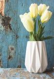 背景蒲公英充分的草甸春天黄色 在一个白色花瓶的郁金香 免版税库存图片
