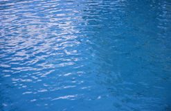 背景蓝色水面 起波纹的纹理水 游泳池表面 免版税库存图片
