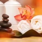 背景蜡烛开花温泉毛巾黄色 在异乎寻常的植物,美丽的兰花的白色毛巾 免版税图库摄影
