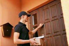 背景配件箱发运英俊查出在服务白色工作者 与包裹的传讯者在客户门附近 免版税库存图片