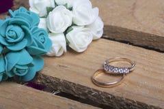 背景钮扣眼上插的花看板卡装饰装饰邀请婚姻白色的珍珠玫瑰 人造花花束和婚戒在一个木箱说谎 免版税库存图片